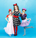 Glamour woman and two girls in party costumes on blue background Stock Photography
