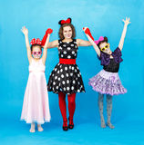 Glamour woman and two girls in party costumes on blue background Royalty Free Stock Photos