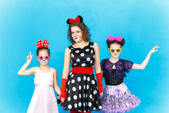 Glamour woman and two girls in party costumes on blue background Royalty Free Stock Image