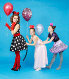 Glamour woman and two schoolgirls with balloons in carnival cost Stock Image
