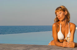 Glamour woman in white bikini in infinity pool Royalty Free Stock Photo