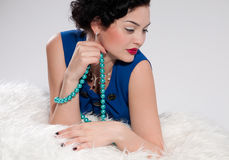Glamour woman on white fur. Beads Stock Photos