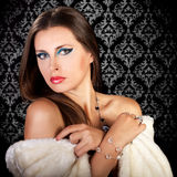 Glamour woman in white fur on vintage black background. Beautiful glamour woman in white fur on vintage black background. Fashion and glamour style. Winter theme Stock Images