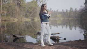 Glamour woman in white pants, jeans jacket and sunglasses standing on the riverbank. The girl is cold, she rubbing her