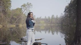 Pretty young woman in white pants, jeans jacket and sunglasses standing on the riverbank. The girl is cold, she rubbing