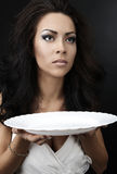 Glamour woman with a white porcelain plate Stock Images