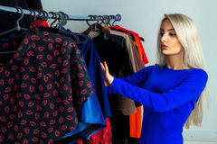 Glamour young blonde lady in clothing store Stock Photos