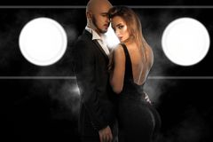 Glamour young couple in black suits hugs in studio Royalty Free Stock Images