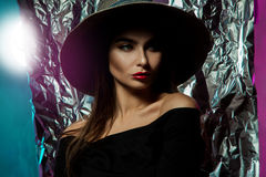 Glamour young lady in hat with wide brim. And red lips looking away in studio on multicolor background royalty free stock image