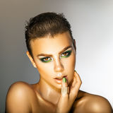 Glamour young woman with green colors makeup looking at camera i Stock Image