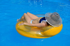 Glamour young woman with a rubber ring in the swimming pool. Legs of a young woman sitting in a rubber disc, the photo in the pool Royalty Free Stock Images