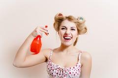 Glamourdehydratie: schitterende grappige blonde pinupdame die de sproeier van de pretholding hebben en in mond bespuiten die came royalty-vrije stock afbeelding