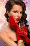 Glamourflicka i röda handskar som rymmer ett exponeringsglas av champagne Dricka champagne Skönhetkvinna med perfekt modemakeup royaltyfri fotografi