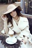 Glamourflickan med mörkt rakt hår bär det lyxiga beigea laget med den eleganta hatten, Royaltyfria Bilder