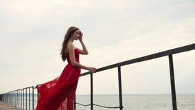 Glamourflickan står på invallning av havet, fullt längdskott stock video