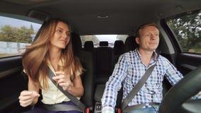 Glamourjongen en meisje die in bedrijfsstijl in de auto in 4K dansen stock videobeelden