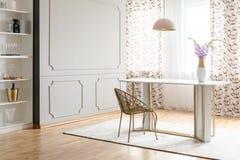 Glamourmatsalinre med en tabell, en stol, en blomma och en tom vägg Förlägga din målning arkivfoton