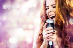Glamourmodekvinna med mikrofonen över bakgrund för blinkabokehnatt Royaltyfria Foton