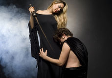 Glamourous blonde lady and her slave. Is down on his knees Royalty Free Stock Image