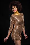 Glamourous lady. In expensive clothes. Interesting unusual make-up with golden coverage, curly hair. Black background in studio. Very beautiful smile expresses Royalty Free Stock Photos
