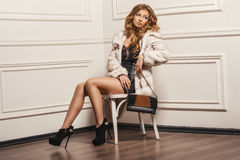 Glamourous portrait of the young beautiful woman in leather boots and stylish handbag. Trend fashion look. Beauty Fashion Model Girl in White Mink Fur Coat Royalty Free Stock Photo