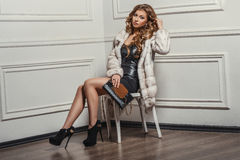 Glamourous portrait of the young beautiful woman in leather boots and stylish handbag. Stock Photography