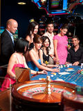 Glamourous roulette players. Group of casino players sitting at a roulette table Royalty Free Stock Photos