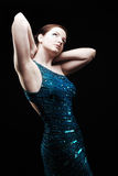 Glamourous woman. Posing in blue sparkly dress royalty free stock photography