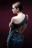 Glamourous woman. Facing to the side in a blue sparkly dress. With a pink glow stock images