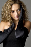 Glamourous woman in black gloves. Young female model wearing long black gloves and black dress Stock Images
