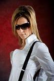 Glamourous young woman wearing sunglasses. Glamourous young woman in sunglasses on dark background Stock Image