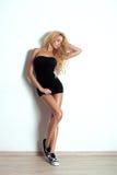 Glamourstående av den sexiga blonda kvinnan. Långt lockigt hår royaltyfria bilder