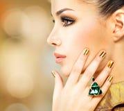 Glamourvrouw met mooie gouden spijkers en smaragdgroene ring Stock Fotografie