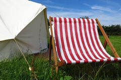 Glamping camping tent at summer music festival. A canvas tent and striped deck chair provide an alluring place to relax and enjoy some solitude in a field in Royalty Free Stock Image