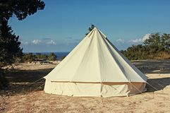Glamping campsite near the sea. Big camping tent for luxury outdoor vacation stock photography