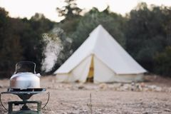 Glamping lifestyle. Boiling kettle with steam near big retro camping tent. Luxury travel accomodation into the forest stock image