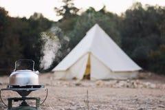 Glampingslevensstijl Kokende ketel met stoom dichtbij grote retro het kamperen tent De aanpassing van de luxereis in het bos stock afbeelding