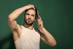 Glamur man hair style. Macho with bearded face and haircut in white singlet. Glamur man hair style. Man brush hair with hairbrush on green background. Haircare stock photos