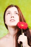 Glamur portrait of long-haired  girl. Long-haired girl with flower over green background Royalty Free Stock Photo