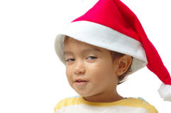 Glance. Child with Santa Claus Red Hat making a curious glance royalty free stock image