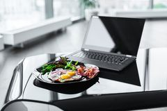 Meal and laptop. Glance table with laptop and morning meals from eggs on dark plate Stock Photography