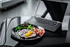 Meal and laptop. Glance table with laptop and morning meals from eggs on dark plate Stock Image