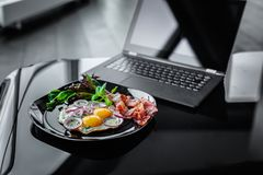 Meal and laptop. Glance table with laptop and morning meals from eggs on dark plate Royalty Free Stock Images