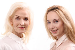 Glances of happy female persons. Cheerful mother and daughter are standing together and looking at camera with smile. Portrait. Isolated Royalty Free Stock Image