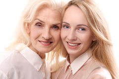 Glances of happy smiling female persons. Mother and daughter are standing together and looking at camera with smile. Portrait Royalty Free Stock Photography