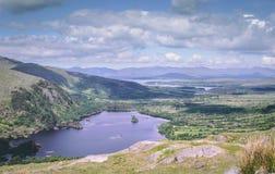 Glanmore sjö på Healy Pass, ett 12 km ruttvärde av hårnålvänd som spolar till och med gränsländerna av ståndsmässig kork och läne Arkivfoto