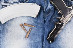 Glansig metallsilverpistol och tidskrift med kulor för anfallgevär på jeans royaltyfri bild