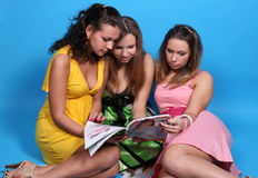 glansig tidskrift läsande tre för kvinnligvänner arkivfoto