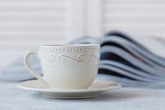 Glansig tidskrift på en tabell, med nolla för mycket grunt djup för kaffekopp Arkivfoto