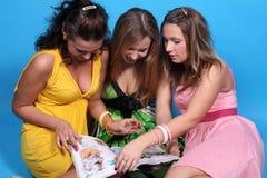 glansiga roliga flickor ha tidskriftavläsning royaltyfri fotografi